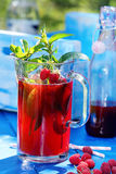 Fresh raspberry juice with mint in the garden. On a blue background Stock Photo