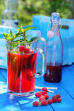 Fresh raspberry juice with mint in the garden. On a blue background Stock Image