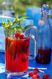 Fresh raspberry juice with mint and lemon. Fresh raspberry juice with mint in the garden on a blue background Stock Photos