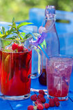 Fresh raspberry juice with mint and lemon. Fresh raspberry juice with mint in the garden on a blue background Royalty Free Stock Images