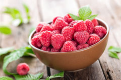 Fresh raspberry with leaves. On wooden background Royalty Free Stock Photos