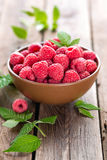 Fresh raspberry with leaves. On wooden background Royalty Free Stock Photo