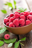 Fresh raspberry with leaves. On wooden background Stock Photos