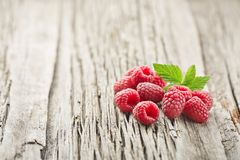 Fresh raspberry with leaves. On a wooden board Stock Images