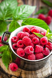 Fresh raspberry with leaves. On wooden table Stock Image