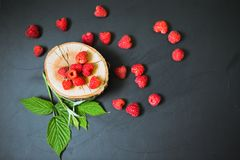Fresh raspberry with leaves on a wooden table outdoors. Fresh raspberry with leaves on a wooden table Royalty Free Stock Photos