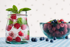 Fresh raspberry mojito. And a glass bowl with berries on a white polka-dotted background Stock Photos