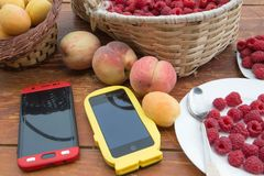 Fresh raspberry, peaches and Apricot, colored smartphone in a wicker basket on wooden table. Healthy food Stock Photos