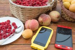 Fresh raspberry, peaches and Apricot, two smartphone in a wicker basket on wooden table. Healthy food Royalty Free Stock Images