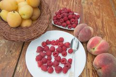 Fresh raspberry, peaches and Apricot in a wicker basket on wooden table. Fresh ripe fruits Stock Images