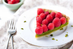 Fresh raspberry and pistachio cream tart. On a white textile background Royalty Free Stock Photography