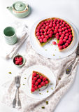 Fresh raspberry and pistachio cream tart. On a white textile background Stock Image