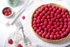 Fresh raspberry and pistachio cream tart. On a white textile background Royalty Free Stock Images