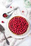 Fresh raspberry and pistachio cream tart. On a white textile background Royalty Free Stock Photo