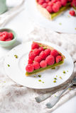 Fresh raspberry and pistachio cream tart. On a white textile background Stock Photo