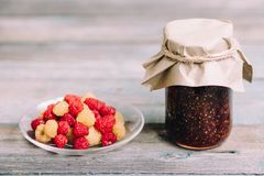 Fresh raspberry on a plate and glass jars with raspberry jam on a wooden table, home-made preparations, cooking, homemade desserts. Raspberry on a plate and royalty free stock photography