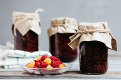 Fresh raspberry on a plate and glass jars with raspberry jam on a wooden table, home-made preparations, cooking, homemade desserts. Raspberry on a plate and stock images