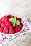 Fresh raspberry in a plate on a wooden table Stock Photos