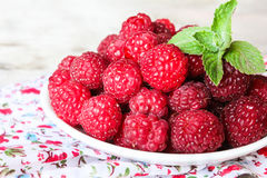 Fresh raspberry in a plate on a wooden table Stock Images