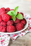 Fresh raspberry in a plate on a wooden table Royalty Free Stock Photos