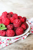 Fresh raspberry in a plate on a wooden table Stock Photography