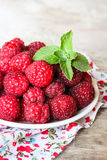 Fresh raspberry in a plate on a wooden table Royalty Free Stock Images
