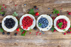 Fresh raspberry, red carrunt and blueberry. Fresh raspberry, red carrunt, blackberrry and blueberry  in cups with fresh leaves, top view Royalty Free Stock Photos