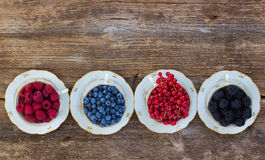 Fresh raspberry, red carrunt and blueberry. Fresh raspberry, red carrunt, blackberrry and blueberry  in cups, top view Royalty Free Stock Images