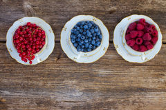 Fresh raspberry, red carrunt and blueberry. With green leaves in cups, top view Stock Photos