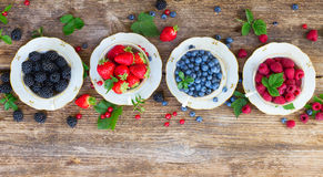 Fresh raspberry, red carrunt and blueberry. Fresh raspberry, strawberry,  blackberrry and blueberry cups in row with fresh leaves, top view Stock Image