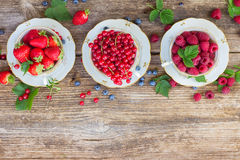 Fresh raspberry , red currand and strawberry. With green leaves in cups, top view Royalty Free Stock Images
