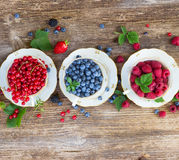Fresh raspberry , red currant and strawberry. Raspberry , red currant and blueberry with green leaves in china cups, top view Stock Photos