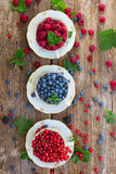 Fresh raspberry , red currant and strawberry. Raspberry , red currant and blueberry with green leaves in cups, top view Stock Photography