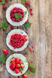 Fresh raspberry , red currant and strawberry. Raspberry , red currant and strawberry with green leaves in cups, top view Stock Images