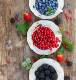 Fresh raspberry, red currunt and blueberry. Fresh  red currant with blackberry and blueberry with green leaves in cups on wooden table, top view Royalty Free Stock Photos