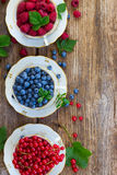 Fresh raspberry, red currunt and blueberry. Fresh raspberry, red currant and blueberry with green leaves in cups on aged wooden table, top view Stock Photography