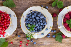 Fresh raspberry, red currunt and blueberry. With green leaves in cups, top view Stock Photography