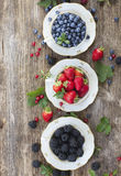 Fresh raspberry, red currunt and blueberry. Fresh strawberry,blackberry and blueberry with green leaves in cups, top view Royalty Free Stock Images