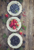 Fresh raspberry, red currunt and blueberry. Fresh strawberry,blackberry and blueberry with green leaves in cups, top view, retro toned Royalty Free Stock Photos