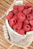 Fresh raspberry. Ripe gooseberry in wooden bucket on white Fresh raspberry in the wooden bucket Stock Photo