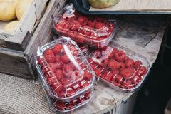Fresh raspberry on sale inside plastic boxes. On top of a wooden table Stock Images