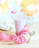 Fresh raspberry smoothie. With sweet lollipop and meringues in background. Fruit cocktail is a light drink made of milk and raspberries, strawberries and other Stock Photo