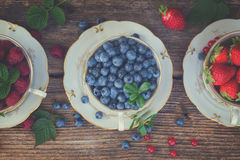 Fresh raspberry, strawberry and blueberry. With green leaves in cups, top view, retro toned Stock Image