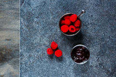 Fresh raspberry. In vintage cup and homemade raspberry jam ( marmalade ) on stone and rustic wooden texture. Dark background layout with free text space. Top Stock Images