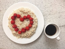 Fresh raspberry in a white plate with porridge. Fresh raspberry in a plate with porridge, round smile shape, raspberry in form oh heart and coffee cup on white Royalty Free Stock Images