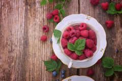 Fresh raspberry on wood. Fresh raspberry in cup with green leaves on wooden background, top view, retro toned Stock Photo