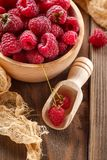 Fresh raspberry in wooden bowl. Wooden bowl with fresh juicy raspberries on wooden background Royalty Free Stock Images
