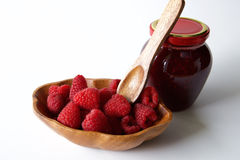 Fresh raspberry in wooden bowl and raspberry jam. In glass jar Stock Images