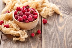 Fresh raspberry in wooden bowl. Wooden bowl with fresh juicy raspberries on wooden background Royalty Free Stock Photography