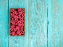 Fresh raspberry in a wooden plate. Photo with copyspace. Fresh raspberry in a wooden plate on blue background. Photo with copyspace Stock Image